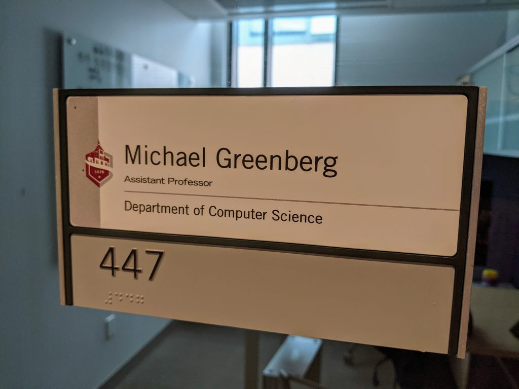 A photo of my office nameplate. The Stevens logo in red, with the following text:  Michael Greenberg Assistant Professor Department of Computer Science  447 447 (in Braille)