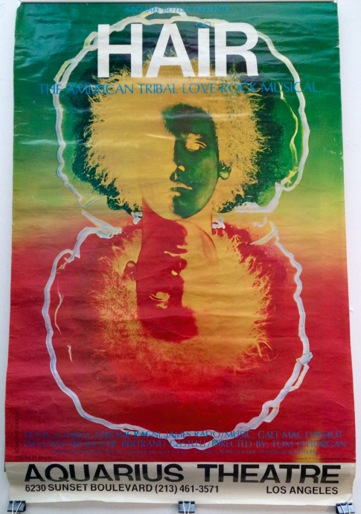 """A vintage poster of """"Hair"""", the American Tribal Love Rock Musical, with a trippy inverted head. This poster advertises a performance at the Aquarius Theatre in Los angeles."""